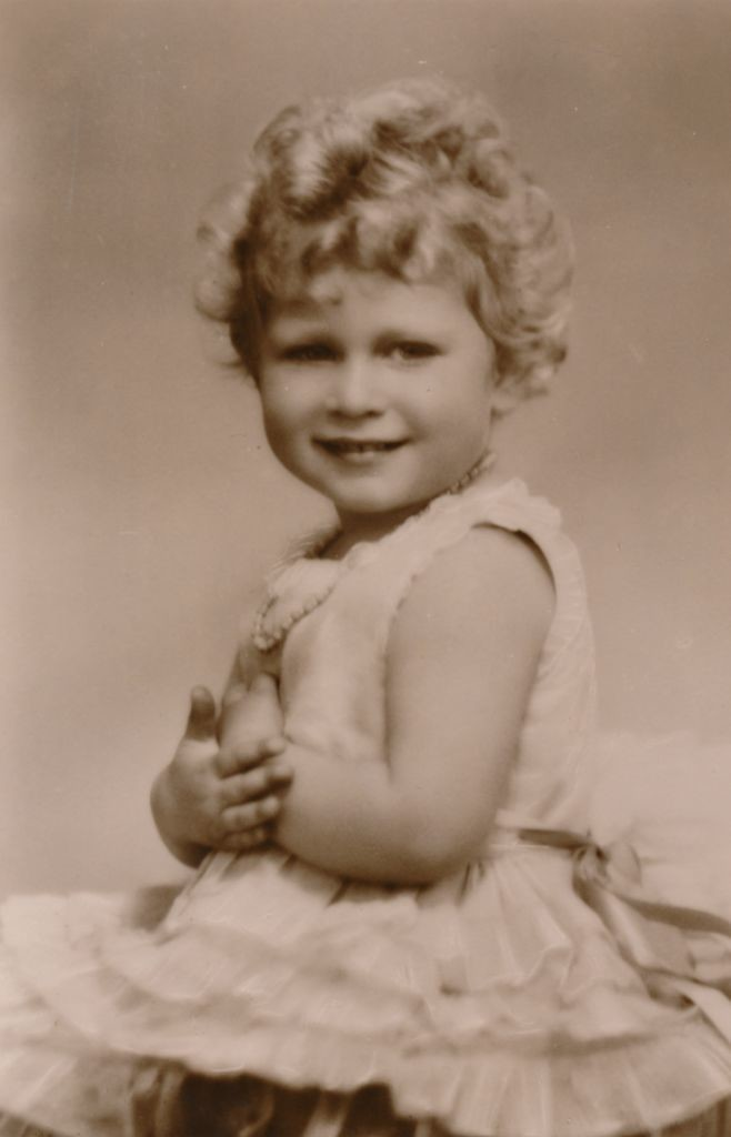 Princess Elizabeth, around age three, smiling at the camera in pearls and ruffles.